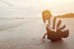 Женщины Indy азиатские усмехаются форма сердца притяжки на пляже песка Стоковое Изображение