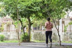 Женщины jogging в дереве предпосылки парка стоковое фото