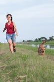 Женщины jogging с собакой Стоковые Изображения