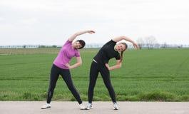 2 женщины stetching outdoors Стоковая Фотография