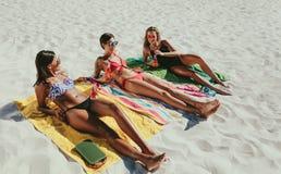 Женщины sunbathing на пляже Стоковая Фотография RF