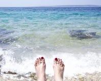 Женщины toes в пене моря на пляже стоковая фотография