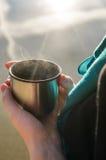 Женщины Youhg держа в ее руках чашка от thermos около озера Стоковые Фото