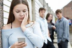 Жертва девочка-подростка задирать обменом текстовыми сообщениями Стоковое Изображение