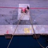 Жестикулируйте запачканного работника дока гавани работая с веревочкой Стоковые Изображения