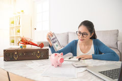 Жесты домохозяйки положили банкноту наличных денег в piggy Стоковая Фотография