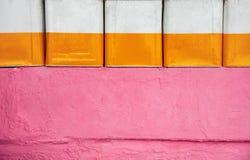 Жестяные коробки декоративно аранжированные на розовой стене стоковое изображение