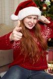 Жест выставки девушки оружия Одетый в ретро красном свитере и шляпе santa Интерьер дома с украшением, елью и подарком рождества Стоковые Изображения