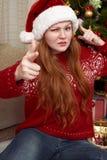 Жест выставки девушки оружия Одетый в ретро красном свитере и шляпе santa Интерьер дома с украшением, елью и подарком рождества Стоковые Изображения RF