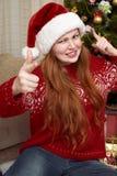 Жест выставки девушки оружия Одетый в ретро красном свитере и шляпе santa Интерьер дома с украшением, елью и подарком рождества стоковое фото