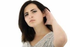 Жест красивой и привлекательной девушки слушая над белым bac стоковое фото