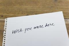 желание вы здесь были рукой написанной на белой бумаге Стоковое фото RF