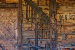 Железная деятельность и заржаветые инструменты и цепи вися на старом woode стоковое изображение rf