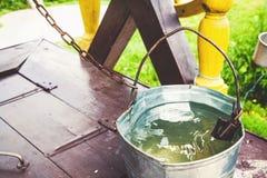 Железное ведро воды стоя на колодце полки Стоковые Изображения