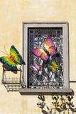 Железное окно с красочными бабочками на желтой стене Стоковые Фотографии RF
