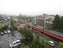 Железнодорожный вокзал, красный поезд, автостоянка, здание и улицы на японской сельской местности Стоковое Изображение