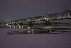 Железнодорожный мост над замороженным рекой в зиме стоковая фотография rf