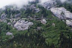 Железнодорожный поезд путешествуя вдоль трассы горы Стоковые Фотографии RF