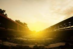 Железнодорожный путь на гравии для sunse транспорта и света поезда Стоковое Изображение RF