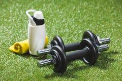 Железные гантели и бутылка воды с полотенцем на траве Стоковое фото RF