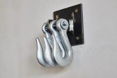 Железные крюки на белой бетонной стене Стоковые Изображения