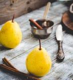 Желтая груша на деревянной доске, ручки циннамона, здоровая закуска Стоковые Фотографии RF
