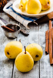 Желтая груша на деревянной доске, ручки циннамона, здоровая закуска Стоковая Фотография RF