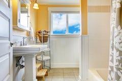 Желтая и белая ванная комната с окном стоковая фотография rf