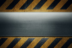 Желтая пакостная grungy поверхность асфальта с черным предупреждением stripes a Стоковое Фото