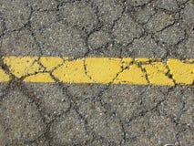 Желтая, покрашенная линия на треснутой дороге Стоковая Фотография RF
