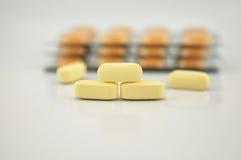 Желтая предпосылка пакета таблетки и волдыря Стоковое Изображение RF