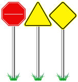 Желтая предупреждающая информация и красные дорожные знаки стопа с травой Стоковые Фотографии RF