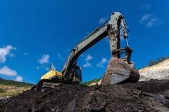 желтая работа backhoe в угольной шахте стоковые изображения rf