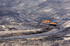 желтая работа backhoe в угольной шахте стоковые фото