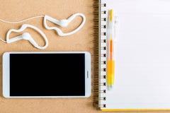 Желтая ручка на тетради и сотовом телефоне с наушником на белом b Стоковая Фотография