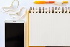 Желтая ручка на тетради и сотовом телефоне с наушником на белом b Стоковое Фото