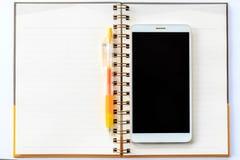 Желтая ручка на тетради и сотовом телефоне Стоковое Изображение RF