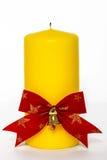 Желтая свеча с красным смычком дальше Стоковая Фотография