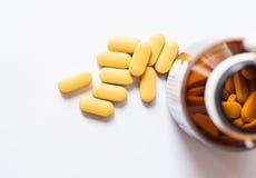 Желтая таблетка от коричневой бутылки на белизне Стоковые Фотографии RF