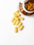 Желтая таблетка от коричневой бутылки на белизне Стоковое фото RF