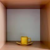 Желтая чашка на деревянной квадратной полке Стоковое Фото