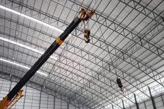 Желтое заграждение крана тележки с крюками в складе Стоковые Изображения