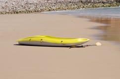Желтое каное лежа на пляже Стоковые Фото
