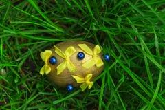 Желтое пасхальное яйцо с смычками Стоковое Фото
