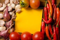 Желтое примечание с чилями, томатом, шалотом и чесноком на деревянной предпосылке стоковые фото
