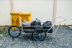 Желтое пластичное мусорное ведро против стены здания стоковые фотографии rf