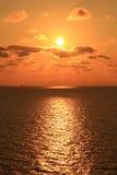 Желтое Солнце установленное в середине океана Стоковая Фотография