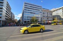 Желтое такси и люди ждать для того чтобы пересечь дорогу на синтагму Афины Грецию стоковые изображения rf