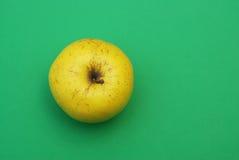 Желтое яблоко на зеленой предпосылке Стоковое Изображение