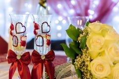 Желтое bride& x27; букет s при 2 wedding бокала украшенного с сердцами Стоковая Фотография